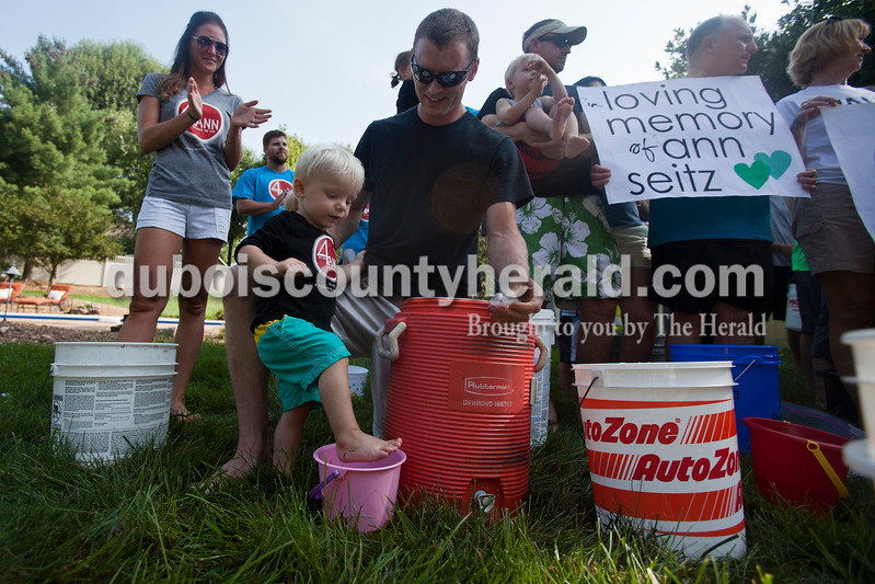 """Caitlin O'Hara/The Herald<br /> Will Werner of Jasper, 1, tested the ice water with his foot while his dad, Maurey, looked on at a gathering of family and friends to complete the Ice Bucket Challenge at Kristen (Seitz) Ruhe's home in Jasper on Saturday. Kristen is the daughter of Ann Seitz who passed away from Amyotrophic Lateral Sclerosis in 2010. The Ice Bucket Challenge is a viral fundraising campaign benefitting The ALS Association, and you can donate at  <a href=""""http://www.alsa.org"""">http://www.alsa.org</a>."""