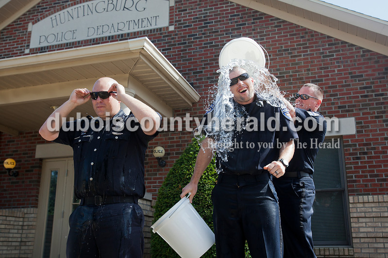 Rachel Mummey/The Herald<br /> Huntingburg Police Officer Josh Hemmer, second from right, squirmed as fellow officer Cody Byrd, right, poured ice water over Hemmer's head, alongside officer Andy Hammack in Huntingburg on Friday. Chief Arthur Parks, Assistant Chief Ronnie Bowman, Det. Sgt. Christian Gogel, and Patrolman Rusty Drew participated in the Ice Bucket Challenge as a department and then challenged Jasper Police, Huntingburg Fire Department and Southridge Athletic Director Brett Bardwell. The trendy facebook phenomenon helps raise money and awareness to Amyotrophic lateral sclerosis, or ALS, a disease that affects nerve cells in the brain and spinal cord that control voluntary muscle movement. ALS is also known as Lou Gehrig's disease.