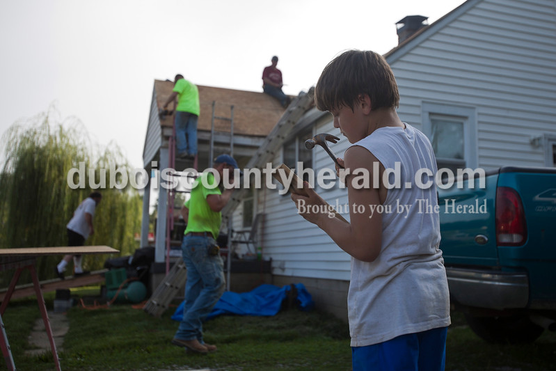 Caitlin O'Hara/The Herald<br /> Denver Wright of Huntingburg, 10, removed old nails from wood planks while volunteer contractors helped to repair his family's roof in Huntingburg on Friday. Denver's father, Mike, far left, was scammed by a fraudulent contractor, and then injured himself trying to re-do the job himself.