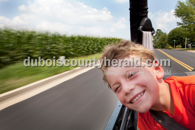 Above: Gabriel McNamee of McCordsville, 7, felt the wind on his face as he rode in the back of his grandfather's Jeep, Jim Jahn of Jasper, after a day of golf and tennis during a visit with his brother, Quinn, 5, on July 21. Herald photo by Heather Rousseau.   <b>From Photoshop:</b> Heather Rousseau/The Herald Gabriel McNamee of McCordsville, 7, felt the wind on his face as he rode in the back of his grandfather's Jeep, Jim Jahn of Jasper (not pictured), after a day of gold and tennis during a visit with his brother, Quinn, 5, not pictured.