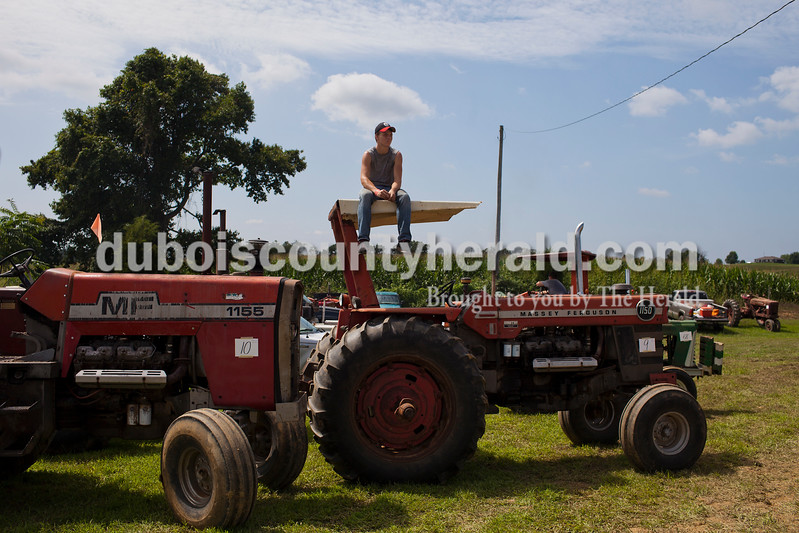 Caitlin O'Hara/The Herald<br /> Dylan Hagemeier of Vincennes sat atop his dad's early 1970s MF 1150 tractor to get a better view of the 32nd annual Celestine Tractor Pull at the Celestine Community Club on Sunday. The event benefitted the Celestine Volunteer Fire Department.