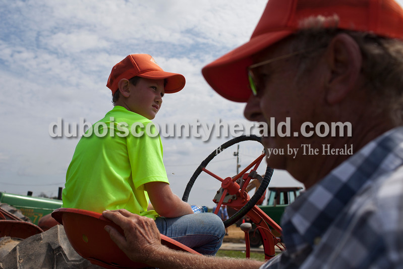 Caitlin O'Hara/The Herald<br /> Russell Mauder of Loogootee, 8, and his grandfather, Ralph, sat atop a 1949 AC WD tractor while they waited for Ralph's turn in the 32nd annual Celestine Tractor Pull at the Celestine Community Club on Sunday. Weidenbenner has competed in the event every year since its debut. The event benefitted the Celestine Volunteer Fire Department.