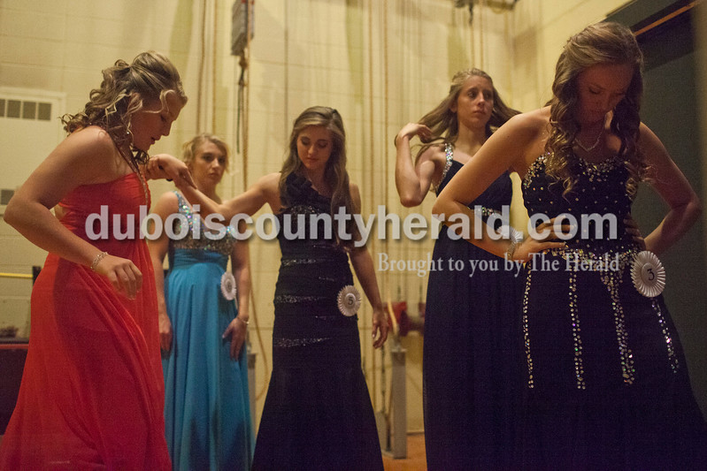 Kendyl McKeough, left, held on to Lauren Meyer, both of Holland, 15, for support as she put on her heels between rounds of the Miss Holland Community Festival Scholarship Pageant on Sunday at Southridge High School. Elli Schank of Holland, 17, second from left, Aubrey Main of Huntingburg, 17, and Bailey Barrett of Huntingburg, 16, waited for their turn in the evening gown round.<br /> Caitlin O'Hara/The Herald
