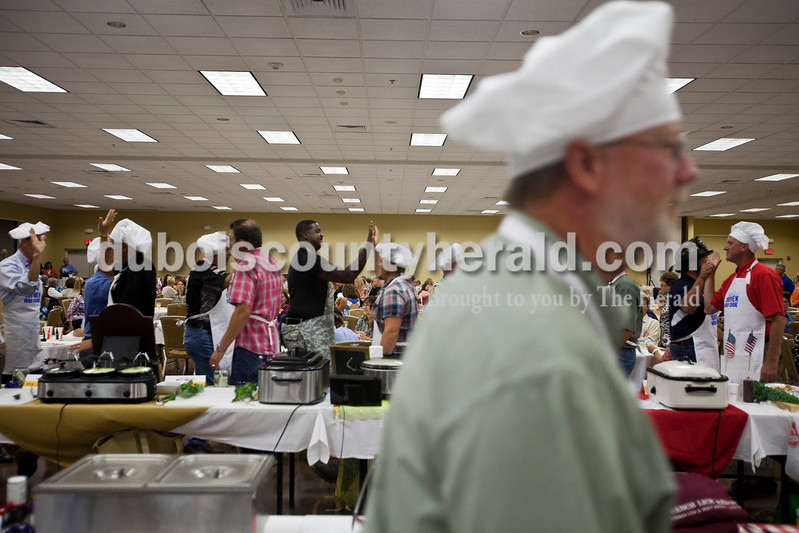Caitlin O'Hara/The Herald<br /> Participants paraded to open the 100 Men Who Cook event on Saturday at the Huntingburg Event Center. The dining event and silent auction benefitted the Indiana National Guard Relief Fund.