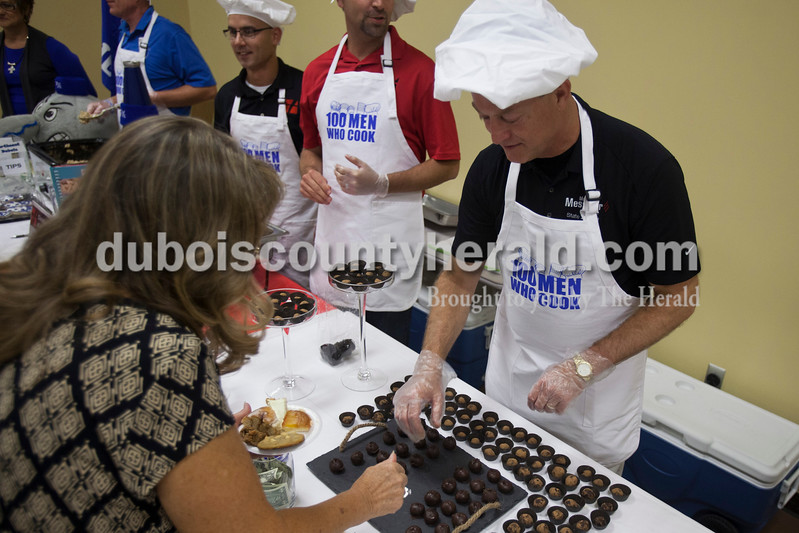 Caitlin O'Hara/The Herald<br /> Mark Messmer of Jasper gave a sample of his chocolate truffles to Donna Welp of St. Anthony at the 100 Men Who Cook event on Saturday at the Huntingburg Event Center. The dining event and silent auction benefitted the Indiana National Guard Relief Fund.
