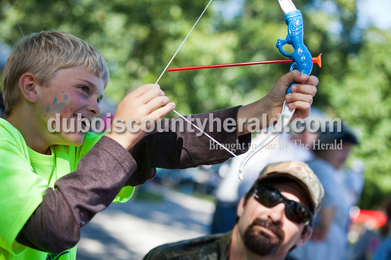 Dawson Hubster of Duff, 8, played with a toy bow and arrow while his dad, Darren, looked on at the Holland Community Festival on Saturday.<br /> Caitlin O'Hara/The Herald