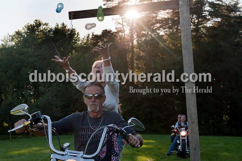 Roger Wever of Springfield drove as his girlfriend Cimaron Lee of Austin tried to catch two water balloons after throwing it over a plank while  competing in the balloon toss field event during the 30th annual ABATE of Indiana Region 10 Southern Hills Bash at the Ireland Sportsman Club on Saturday. Heather Rousseau/The Herald