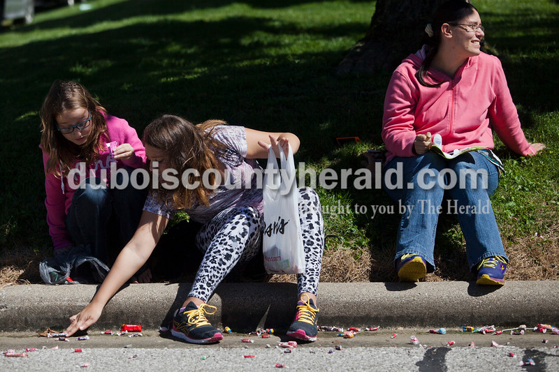 Katelen Jacobson of Holland, 12, center, collected candy while she watched the Holland Community Festival parade with friend Ashlynn Weaver of Huntingburg, 11, left, and Jacobson's mother Darlene, right, on Saturday.<br /> Caitlin O'Hara/The Herald