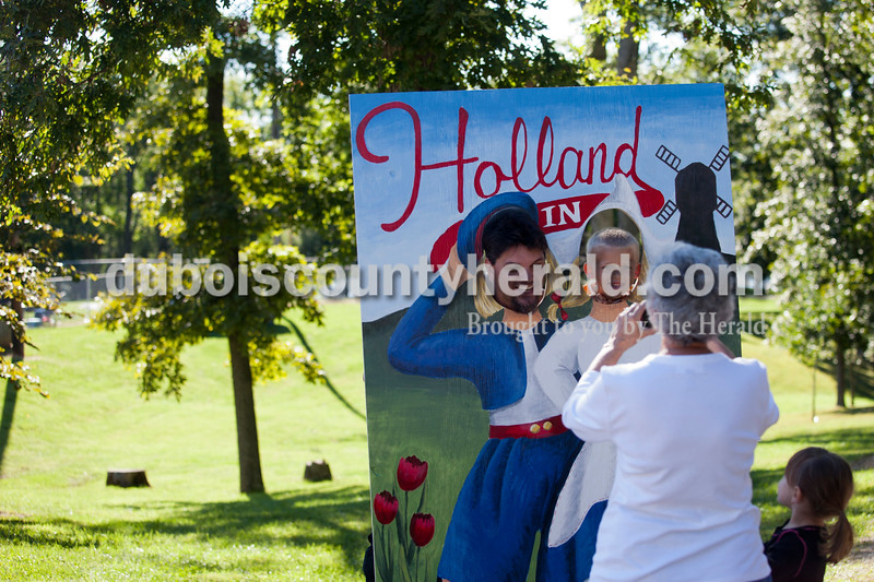 Jeff Dunn of Indianapolis, left, and Case Reinke of Dale, 7, poked their heads through a cutout while Dunn's aunt/Reinke's grandmother Judy Heilman of Santa Claus took their photo at the Holland Community Festival on Saturday. Dunn's daughter, Remington, 3, watched on. <br /> Caitlin O'Hara/The Herald