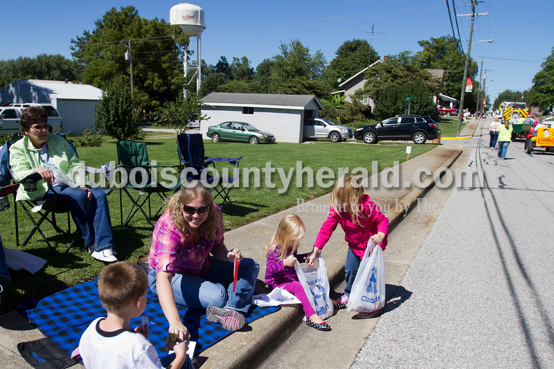 Marisa Thacker of Huntingburg, 5, right, collected candy for her sister, Katie, 2, while their mother, Adriane shared candy with her nephew Jett Springer of Jasper, 5, left, during the Holland Community Festival parade on Saturday.<br />  Caitlin O'Hara/The Herald