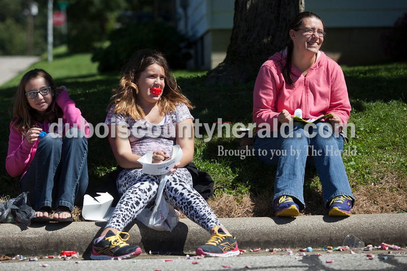 Ashlynn Weaver of Huntingburg, 11, left, Katelen Jacobson of Holland, 12, center, and Jacobson's mother Darlene, right,  watched the Holland Community Festival parade on Saturday.<br /> Caitlin O'Hara/The Herald