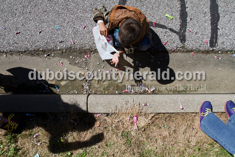 Katelen Jacobson of Holland, 12, left, her brother, Zachary, 7, center and friend Ashlynn Weaver of Huntingburg, 11, right, collected candy from the Holland Community Festival parade on Saturday.<br /> Caitlin O'Hara/The Herald