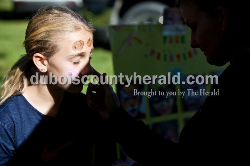 Hannah Burnett of Holland, 11, got her face painted by Huntingburg-native Brandy Miller of Evansville at the Holland Community Festival on Saturday.<br /> Caitlin O'Hara/The Herald