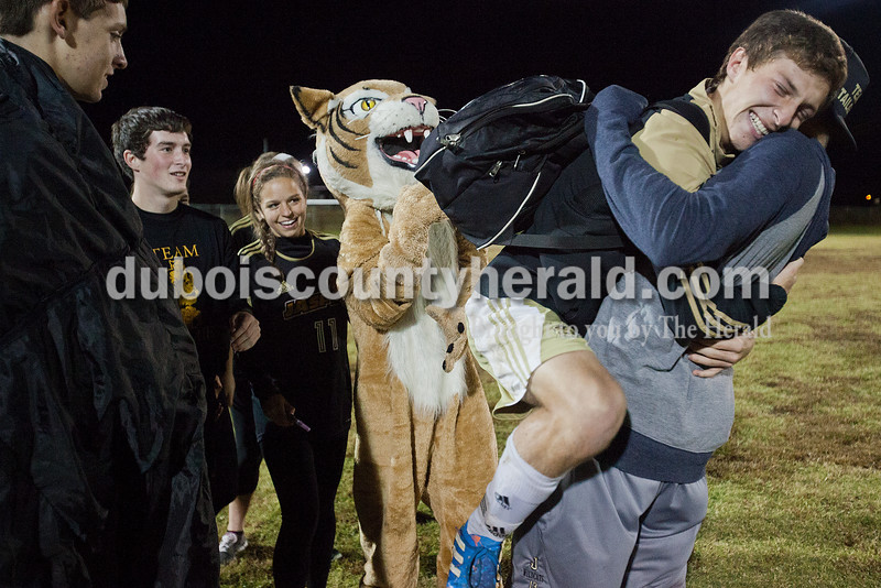 Jasper's Caleb Hurst jumped into the arms of senior Tyler Begle as senior Cameron Mendel, left, sophomore Tyler Nottingham, junior Brittany Haskins and sophomore Carson Pierce, dressed as the Wildcat, greeted members of the Jasper boys soccer team after their 4-1 victory over Castle during Monday night's IHSSA boys soccer sectional at North High School Soccer Complex in Evansville. Rachel Mummey/The Herald