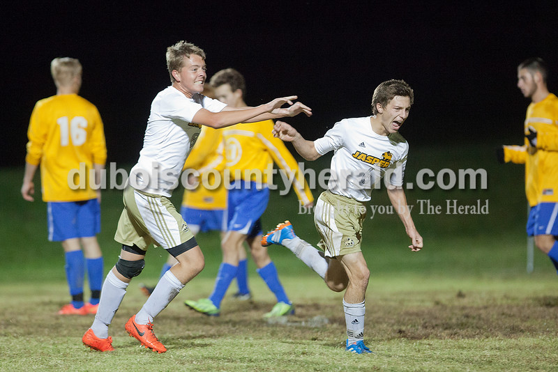 Jasper's Mitchell Flynn, left, and Caleb Hurst celebrated a goal scored by Hurst in the second half during Monday night's IHSSA boys soccer sectional at North High School Soccer Complex in Evansville. Jasper defeated Castle 4-1. Rachel Mummey/The Herald