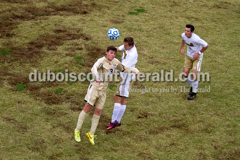 Jasper's Garrett Jesperson headed the ball away from Washington's Colten Garland during the 2A sectional final Saturday in Evansville. Jasper's Luke Ackerman, right, looked to help. The Wildcats won 3-0. <br /> Caitlin O'Hara/The Herald