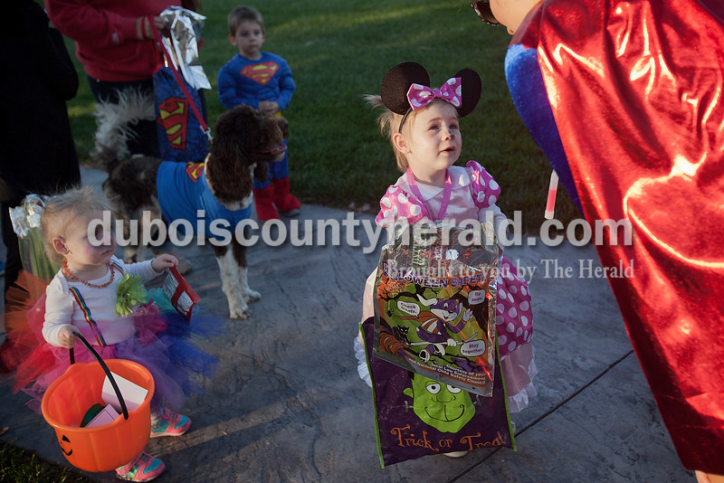 Rachel Mummey/The Herald<br /> Nalanie Buechlein of Jasper, 2, toted bags of candy while trick-or-treating with her sister one-year-sister Brynn, right, and Hunter Erny of Jasper, 2, with his Superdog Homer on Sunday during the fourth annual Halloween at Central Green. The Jasper Parks and Recreation Department sponsored the trick-or-treat event which also hosted pumpkin bowling, corn hole, ring toss and other games.
