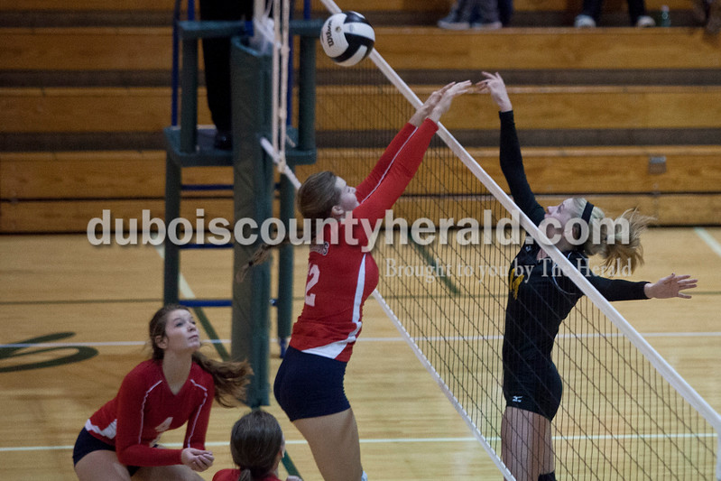Heritage Hills' CJ Nance, center, and April Kippenbrock, left, attempted to block a spike by Jasper's Teyah Leinenbach during the sectional Saturday at Vincennes Lincoln. The Wildcats swept the Patriots 3-0.<br /> Caitlin O'Hara/The Herald