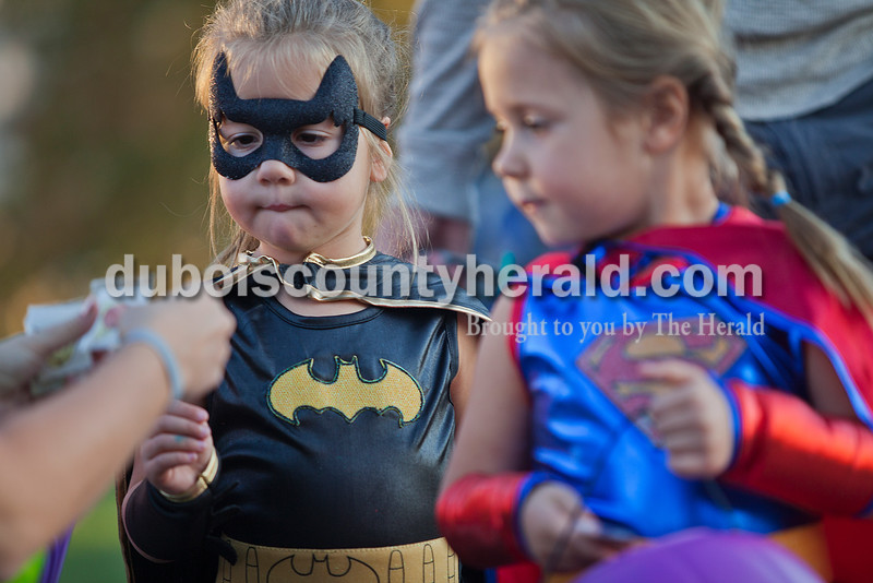 Rachel Mummey/The Herald<br /> Lilly Bajorek of Jasper, 4, left, and her twin sister Diana donned superhero costumes while collecting prizes Sunday during the fourth annual Halloween at Central Green. The Jasper Parks and Recreation Department sponsored the trick-or-treat event which also hosted pumpkin bowling, corn hole, ring toss and other games.