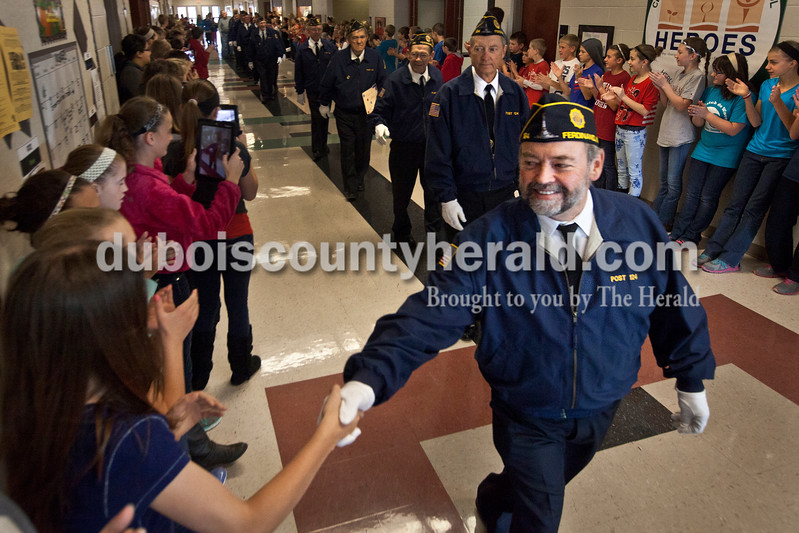 "Heather Rousseau/The Herald<br /> Veteran Jim Schnieders with the Ferdinand American Legion post 124 shook hands with Cedar Crest sixth-grader Kelsey Mehling as students lined the hallway and applauded the veterans during a Veterans Day event at Cedar Crest Intermediate School in Bretzville this morning. More photos are at  <a href=""http://www.DuboisCountyHerald.com"">http://www.DuboisCountyHerald.com</a>."