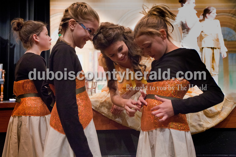"Kelsey Graman, 18, of Jasper, center, helped Denni Hilgefort, right, with her costume as Brianna Williams, 10, of Jasper, left, watched. They were preparing for the ""Be Our Guest"" song and dance scene during The Children's Theatre Project  dress rehearsal of Disney's Beauty and the Beast Jr. at Jasper Middle School in Jasper on Sunday. Graman was dressed as Bell and the other girls as napkins. Heather Rousseau/The Herald"