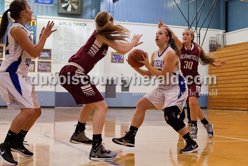 Northeast Dubois' Liz Huebner, second from right, went up for a shot with assistance from teammate Jenna Stemle, left, while being guarded by Bloomfield's Kylee Moody, second from left, and Emily Bucher, right, during Tuesday night's game in Dubois. The Jeeps won 60-59. Rachel Mummey/The Herald