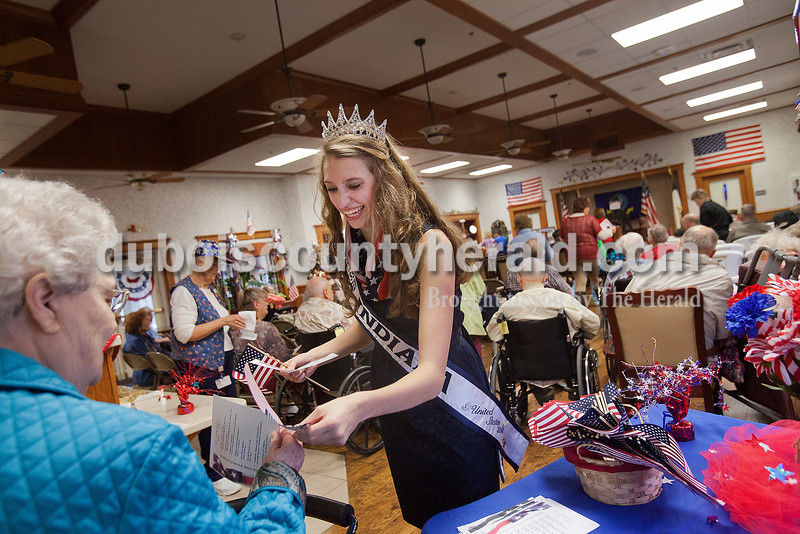Miss Teen Indiana Priscilla Olson of Jasper, 15, handed out programs and flags at Northwood Retirement Community before the start of their Veterans Day service on Tuesday in Jasper. Rachel Mummey/The Herald