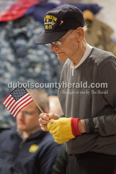 Northwood Retirement Community resident Roman Kiefer stood with a flag to be recognized as a veteran during the Veterans Day service on Tuesday in Jasper. Kiefer was on the USS Princeton when it sank during WWII. He held on to a life raft waiting to be rescued for four hours. Rachel Mummey/The Herald