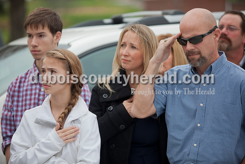 "Rachel Mummey/The Herald<br /> SFC Anthony ""Tony"" Hurst of Jasper, left, his wife Jennifer and their children Hailey, 14, and Anthony Jr., 16, saluted the flag during the playing of Taps following a ceremony honoring him with this year's Living Veteran Award at the American Legion Post 493 in St. Anthony on Saturday. Hurst served as a Marine and then the U.S. Army in Japan, Kuwait and Iraq. He has survived eight IED explosions, trained soldiers and captured enemy insurgents."