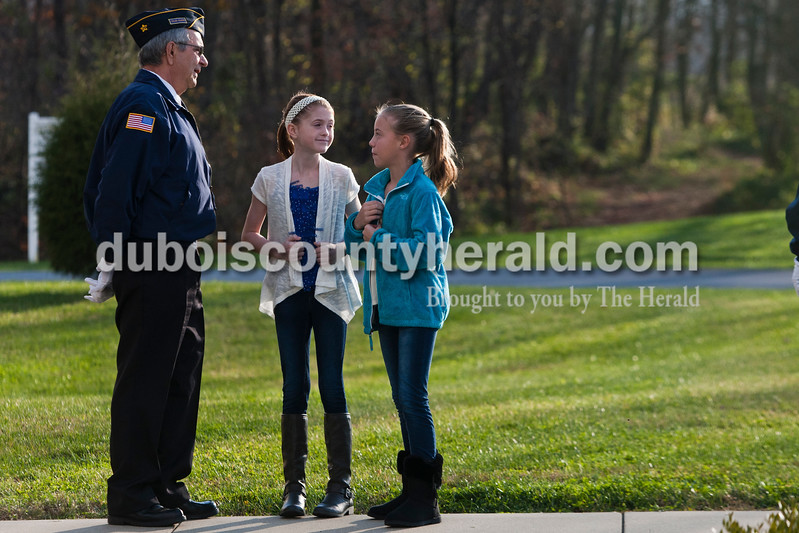 Larry Hamilton with the Ferdinand American Legion post 124 spoke with his grandchildren sixth-grader Ava Hamilton, center, and fifth-grader Amy Wahl  at Cedar Crest Intermediate School in Bretzville this morning after an event hosted by the school to honor the veterans. Heather Rousseau/The Herald