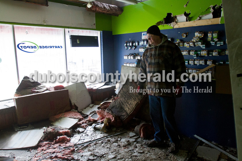 Caitlin O'Hara/The Herald<br /> Cartridge Depot owner Mike Jones of Loogootee surveys damage to his shop on Nov. 13 in downtown Loogootee.