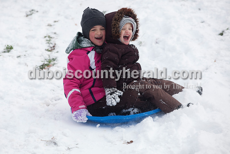 Haven Weyer, 7, and her sister Haisley, 3, sled down a hill in their neighborhood in Ferdinand on Monday. Ferdinand received four inches of snow and schools were closed. Rachel Mummey/The Herald