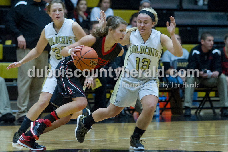 Southridge's Kadie Dearing dribbled past Jasper's Katelyn Hedinger and Nicolette Eckert as they defended during the game against Saturday in Jasper. The Raiders beat the Wildcats 49-47.<br /> Caitlin O'Hara/The Herald