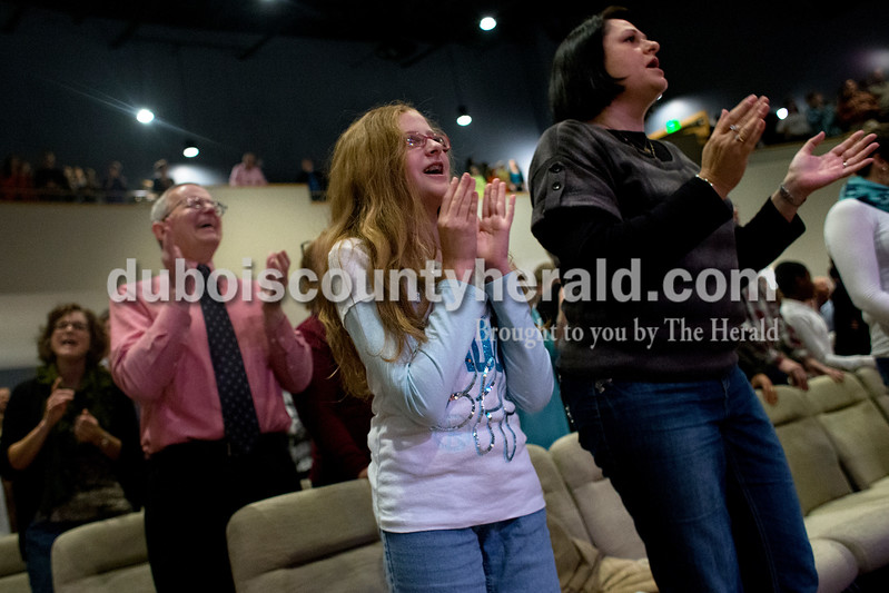 Isabella Ross of Jasper, 11, middle, and her mother, Shannon, sang along to the music during Sunday's service in the Christian Church of Jasper's new worship center. Dave Weatherwax/The Herald