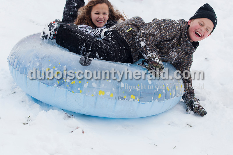 Leo Alvis, 9, and his sister Magda, 11, laughed while sledding down a hill in their neighborhood in Ferdinand on Monday. Ferdinand received four inches of snow and schools were closed. Rachel Mummey/The Herald