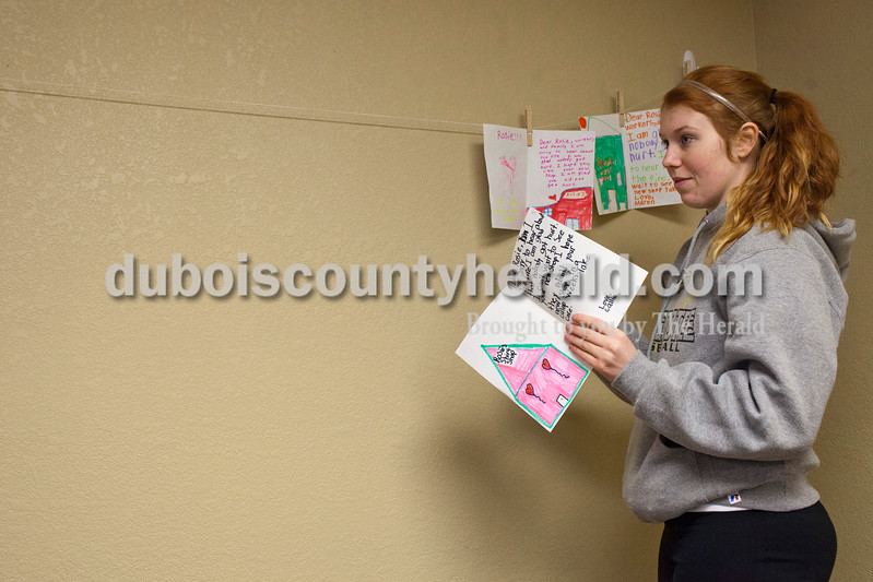 Caitlin O'Hara/The Herald<br /> Rosie Bridges' daughter Chassidy of Loogootee hung cards sent to the family and employees of Rosie's made by Loogootee Elementary School studnets in a temporary space they will use as Rosie's Shirt Shop on Saturday following a major fire downtown Loogootee that has left a block in disrepair. Bridge's old shop is across the street, and she plans to rebuild as soon as possible.