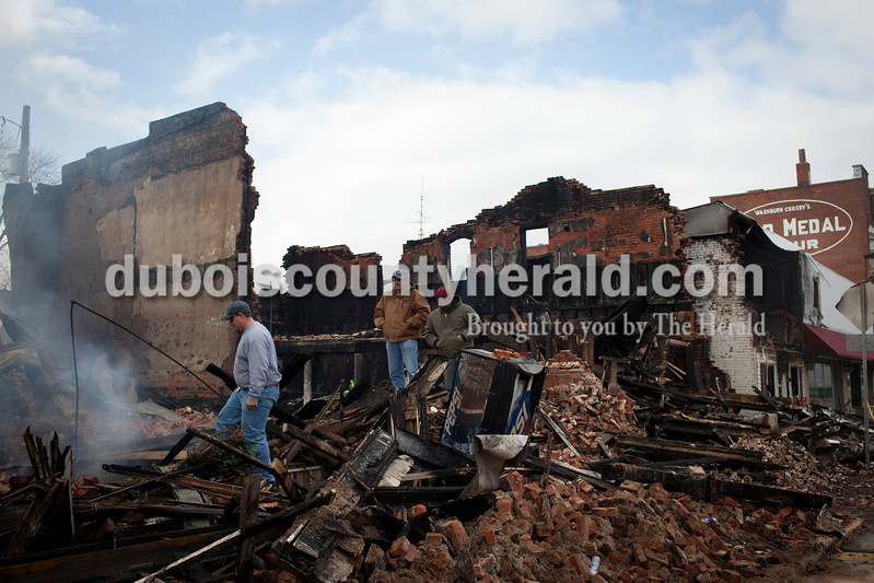 Caitlin O'Hara/The Herald<br /> Loogootee firefighters Eric Thomas, left, Wayne Mersinger, center, and Ethan Mathies, right, survey smoldering rubble on Nov. 13 in Loogootee.