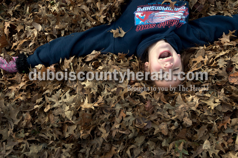 Heather Rousseau/The Herald<br /> Cali Mehringer of Jasper, 12, laughed while playing in a pile of leaves while volunteering with St. John Bosco Youth Ministries to rake the yard of Linda Bieker in Jasper on Saturday. The group volunteered to rake four yards of area residents this weekend.  Bieker gave the girls hot chocolate and cookies when they were done with her yard.