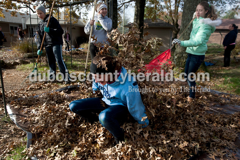 Heather Rousseau/The Herald<br /> Chloe Lueken of Jasper, 15, leapt from a pile of leaves as Genna Uebelhor of Ferdinand, 12, right, raked leaves into the pile while volunteering with St. John Bosco Youth Ministries to rake the yard of Linda Bieker on Saturday in Jasper. The group volunteered to rake four yards of area residents this weekend.  Bieker gave the girls hot chocolate and cookies when they were done with her yard.<br /> <br /> The group volunteered to rake four yards of area residents this weekend.  Bieker gave the girls hot chocolate and cookies when they were done with her yard.