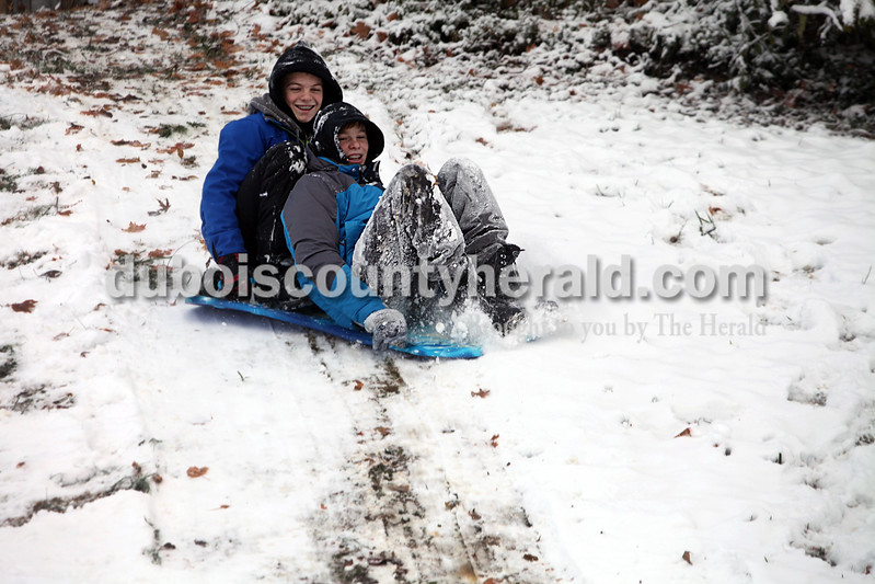 Heather Rousseau/The Herald<br /> Dimitry Gordon, 14, left, and his brother Quintin Gordon, 15, sledded down a hill in an open space behind First Presbyterian Church near their home in Jasper this morning. Quintin was glad schools were closed due to snow while Dimitry would have preferred to go to school.