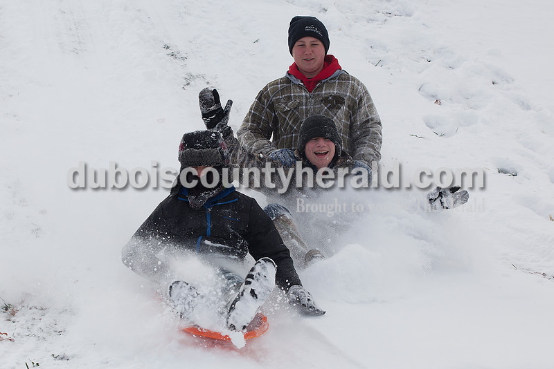 Corbin Bell, 12, Zach Hopf, 13, and Ian Treat, 13, all of Ferdinand, sled down a hill at 18th St. Park in Ferdinand on Monday. Ferdinand received four inches of snow and schools were closed. Rachel Mummey/The Herald