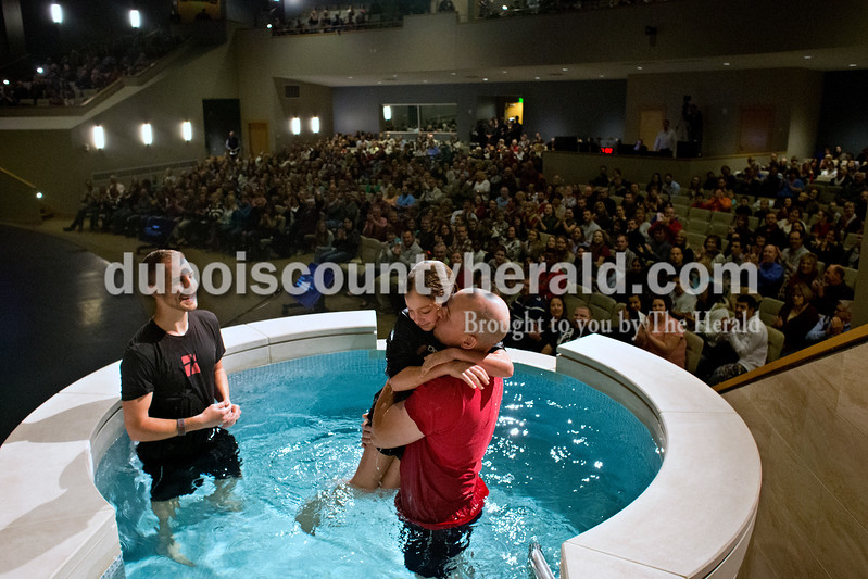 Dave Weatherwax/The Herald<br /> Drew Thurman, left, the family life and teaching minister at Christian Church of Jasper, watched as Scott Smith of Huntingburg kissed his daughter Katie, 9, after she was baptized Sunday morning as the Jasper church hosted its first services in the new 1,000-seat worship center. More than 1,800 people attended the two morning services.