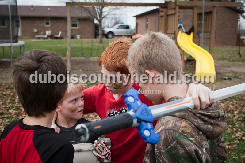 Caitlin O'Hara/The Herald<br /> Aiden Pieper, 11, center, held a team strategy meeting with his brother Noah Pieper of Ireland, 9, center left, and neighbors Travis Lechner, left, and Ajay Sermersheim, 12, right, during a backyard melee Sunday in Ireland. The team game, consisting of kids from five neighboring families, was based off of the military video game Call of Duty. The boys have lived in the same neighborhood together for most of their lives.