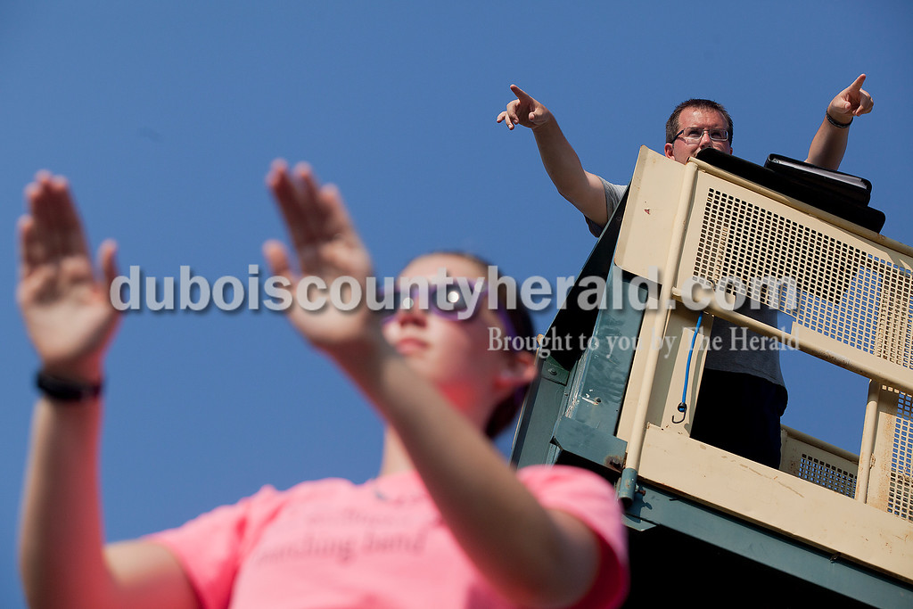 Perched from a birds eye view on a mechanical lift, Forest Park Marching Band Director Chad Gayso points out directions while backing up drum major junior Alyssa Hurm during practice at Forest Park High School. Rachel Mummey/The Herald