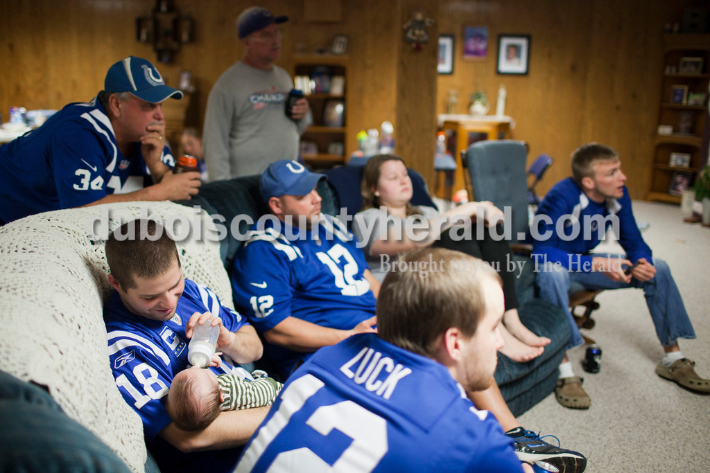 """Caitlin O'Hara/The Herald<br /> Adam Hopf of Ireland, left, fed his son, Cayden, 2 months, while his friends and neighbors watch the Colts game Sunday at the Blackgrave family's home in Ireland. The group get together every week to watch football. """"We have religion Sunday morning and then this is the religion in the afternoon,"""" Tim Herbig of Ireland, who was also present, said with a laugh."""