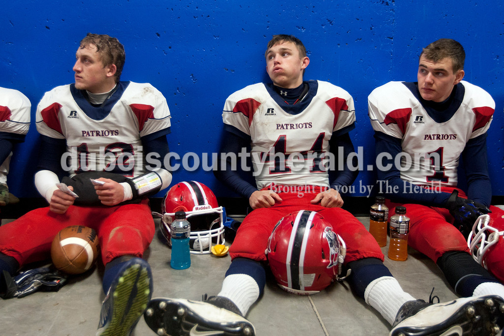 Heritage Hills' Logan Wilkerson, left, Ethan Griepenstroh, and Casey Miller rested during halftime of the Class 3A regional against Charleston at Dutch Reis Field in Charlestown. The Patriots won 28-7.<br /> Heather Rousseau/The Herald