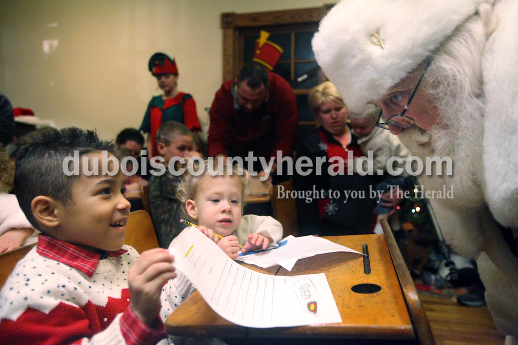 Heather Rousseau/The Herald<br /> Cruz Lytle of Santa Claus, 5, left, and Aspen Saunderson of Birdseye, 2, showed Santa letters they were writing to him while at the Santa Claus Museum and Village on Monday evening in Santa Claus. From Dec. 1 throughDec. 20 children sit at antique school desks in the original Santa Claus Post Office and write their letters to Santa Claus.