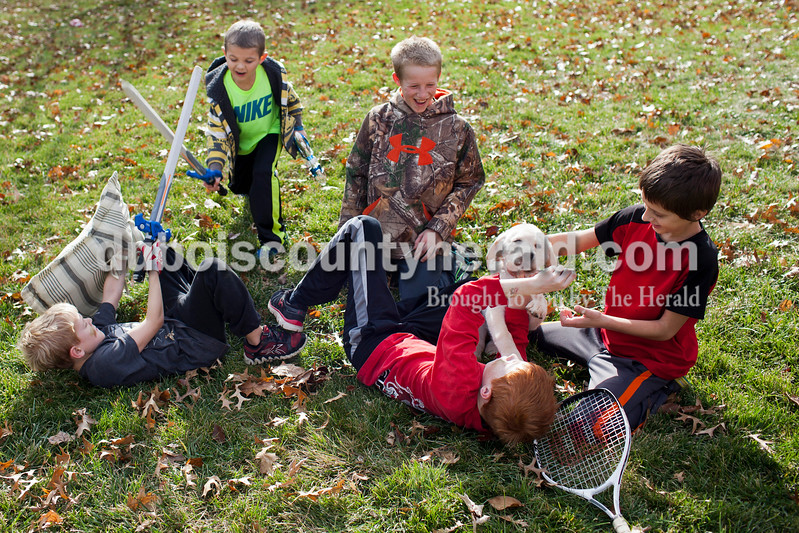 Caitlin O'Hara/The Herald<br /> From left, Noah Pieper, 9, Jack Kluemper, 5, Alex Sermersheim, 12, Aiden Pieper, 11, and Travis Lechner, 11, all of Ireland, battled during a backyard melee Sunday in Ireland. The Pieper family labrador mix puppy, Hoosier, served as the fierce K-9 unit. The team game, consisting of kids from five neighboring families, was based off of the military video game Call of Duty. The boys have lived in the same neighborhood together for most of their lives.