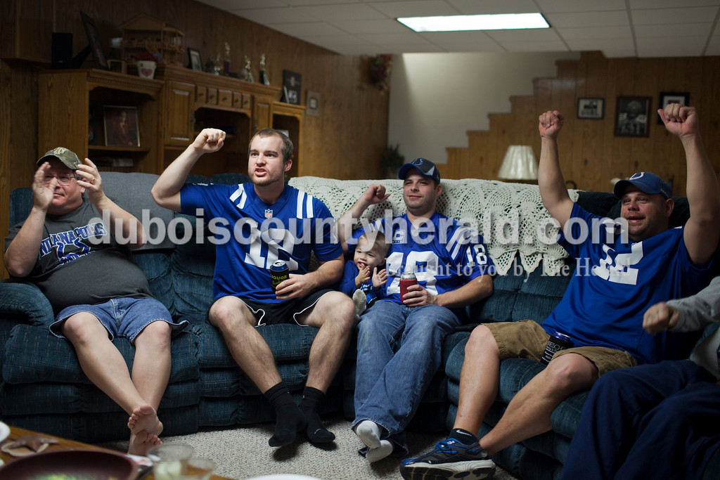 """Caitlin O'Hara/The Herald<br /> Kevin Blackgrave, left, his son Josh, Adam Hopf and his son, Gavin, 2, and Bubba Wilz, all of Ireland, watch the Colts game Sunday at the Blackgrave's home in Ireland. The friends and family get together with other families in the neighborhood every week to watch football. """"We have religion Sunday morning and then this is the religion in the afternoon,"""" Tim Herbig of Ireland, who was also present, said with a laugh."""