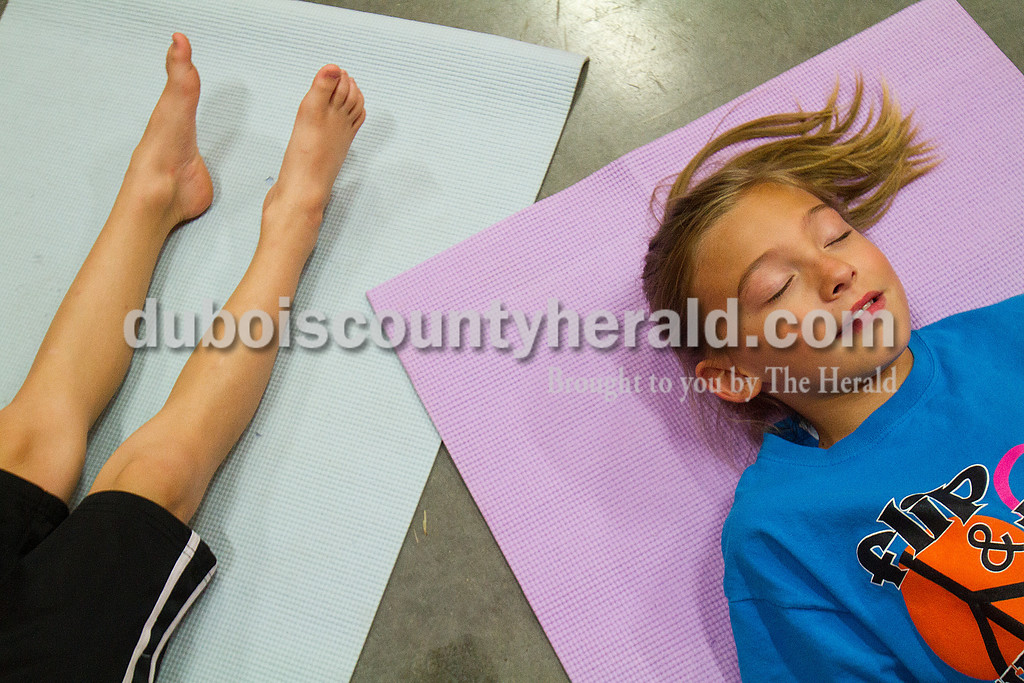 Braelyn Houchin of Huntingburg, 8, right, and her brother Bryton, 5, practiced Savasana, or corpse pose, during a children's yoga session led by Amanda Gamble at the YMCA. Rachel Mummey/The Herald